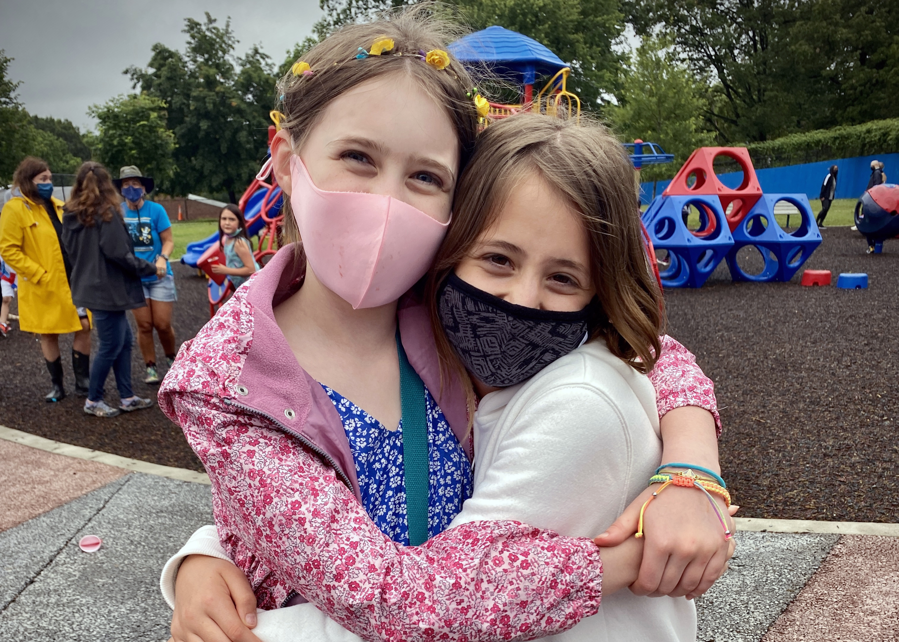 Two students hugging in masks at 5th grade celebration
