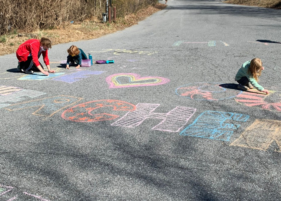 A group of parents and students wearing masks write with chalk on the Sligo Creek Elementary School sidewalk