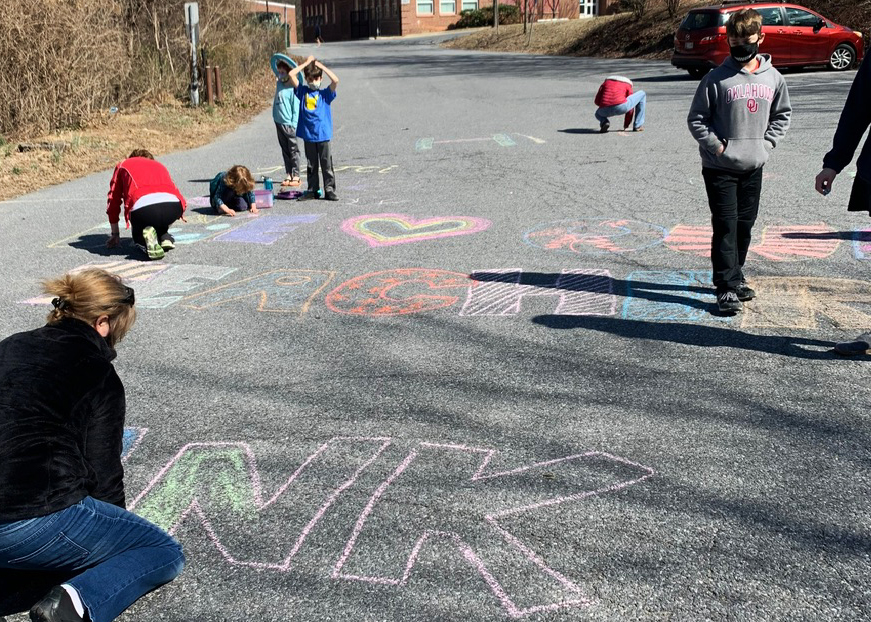 A group of parents and kids chalk messages welcoming teachers back to SCES