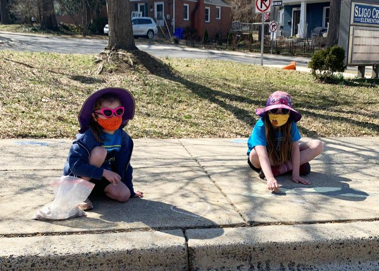 Two students in sun hats and sunglasses wearing masks write with chalk on the Sligo Creek Elementary School sidewalk