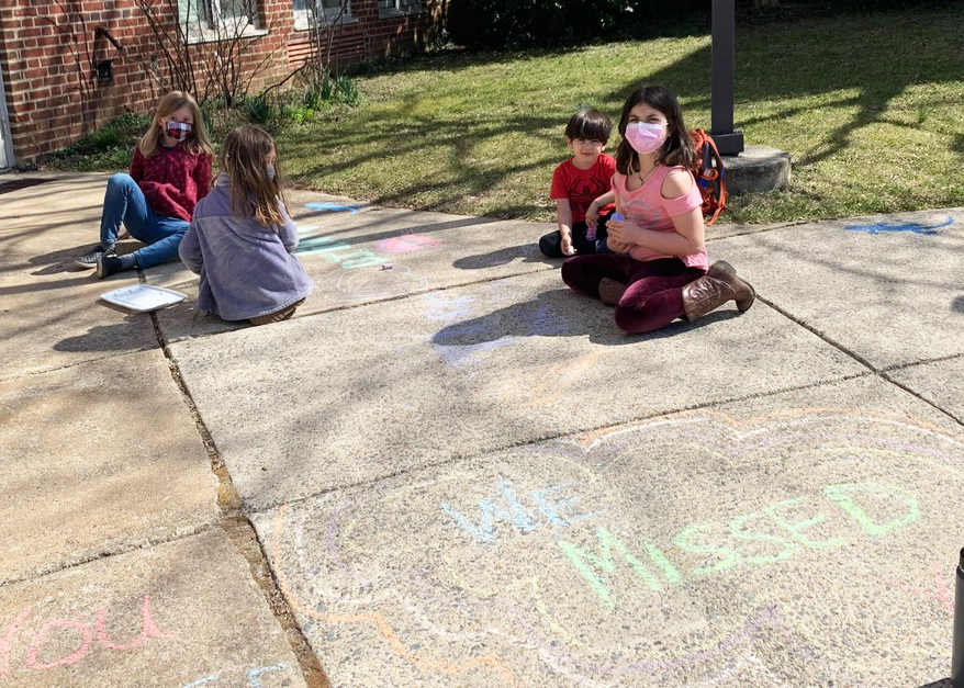 A group of students chalk colorful messages welcoming teachers back to SCES
