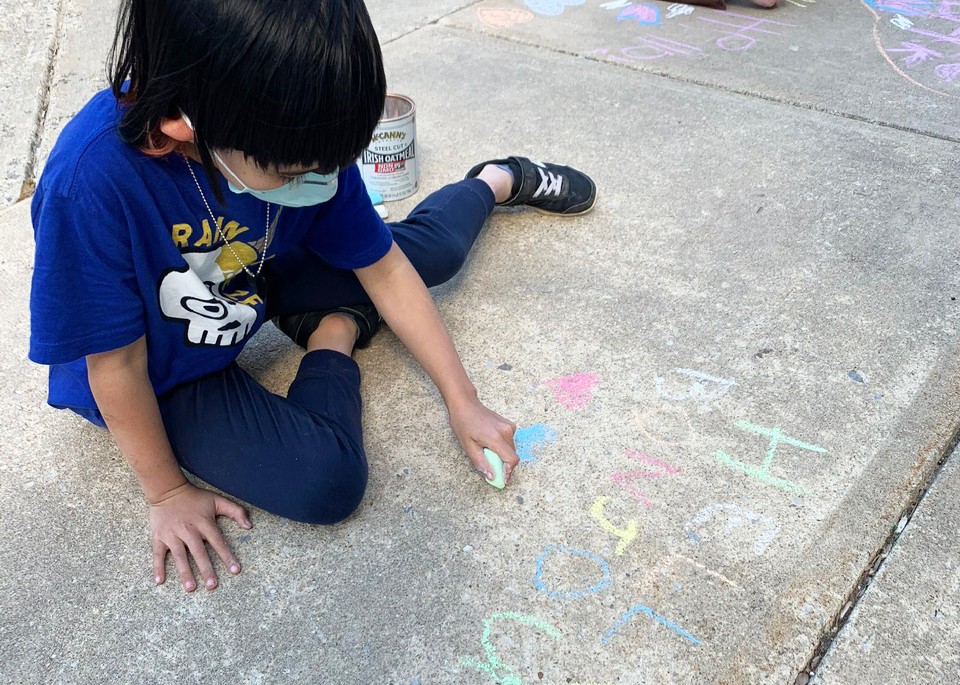 Young girl chalks messages in English and French on the sidewalk in front of Sligo Creek Elementary School