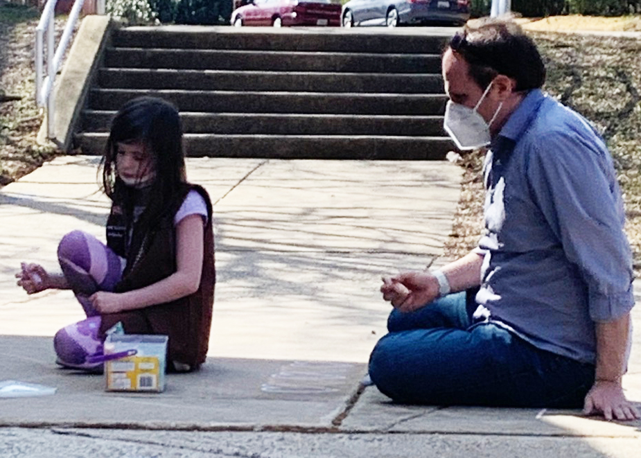 Father and daughter wearing masks write chalk messages in front of Sligo Creek Elementary School