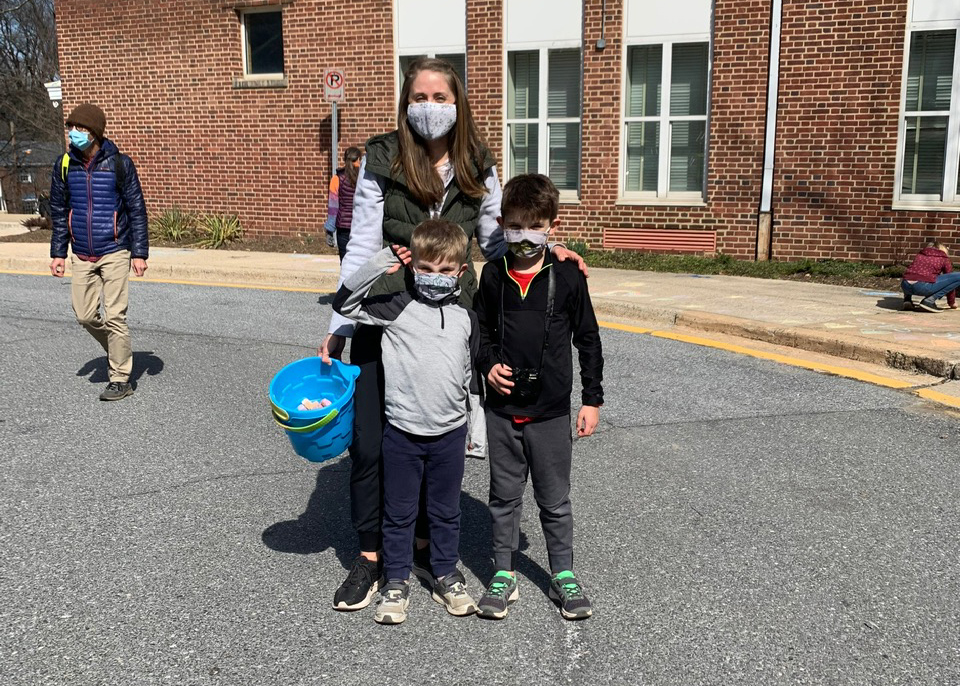 A mom and her two children wearing masks carrying a bucket of chalk