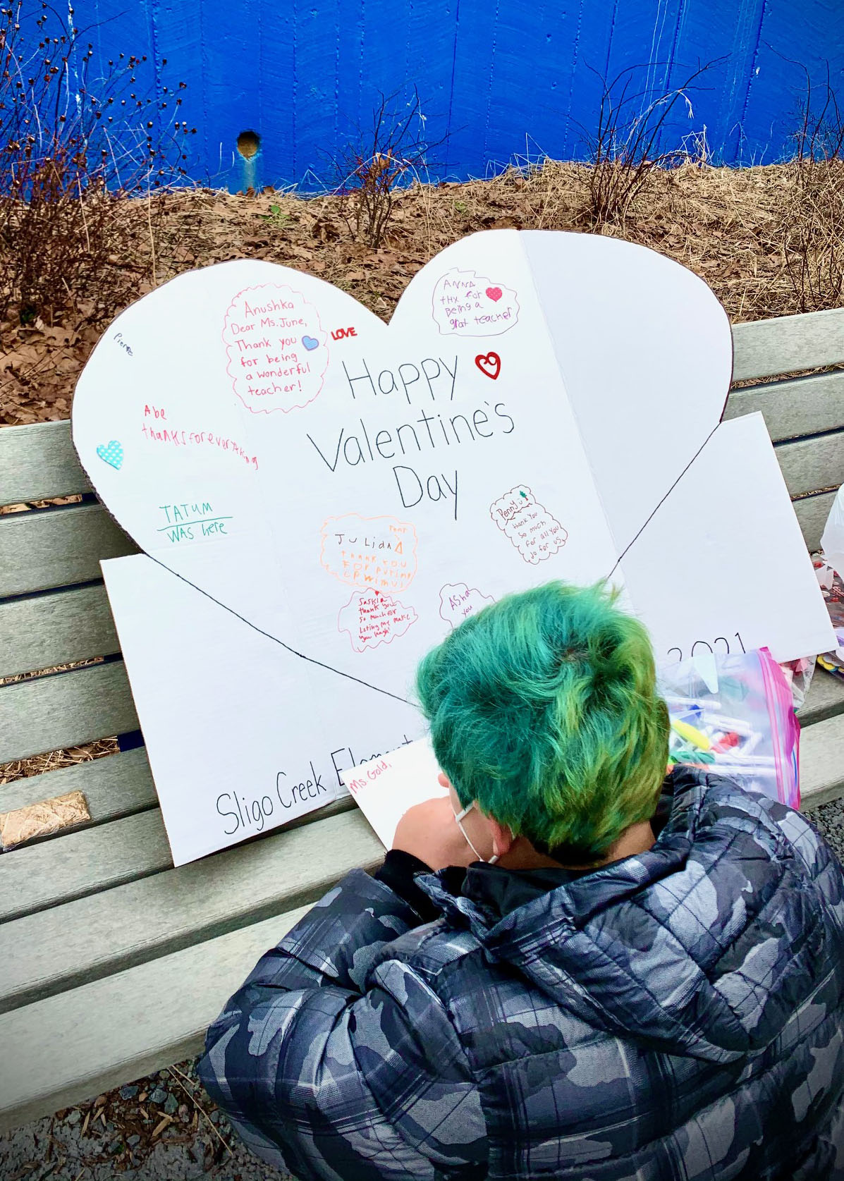 Young boy with colorful hair signs a Valentine's Day card for his teacher