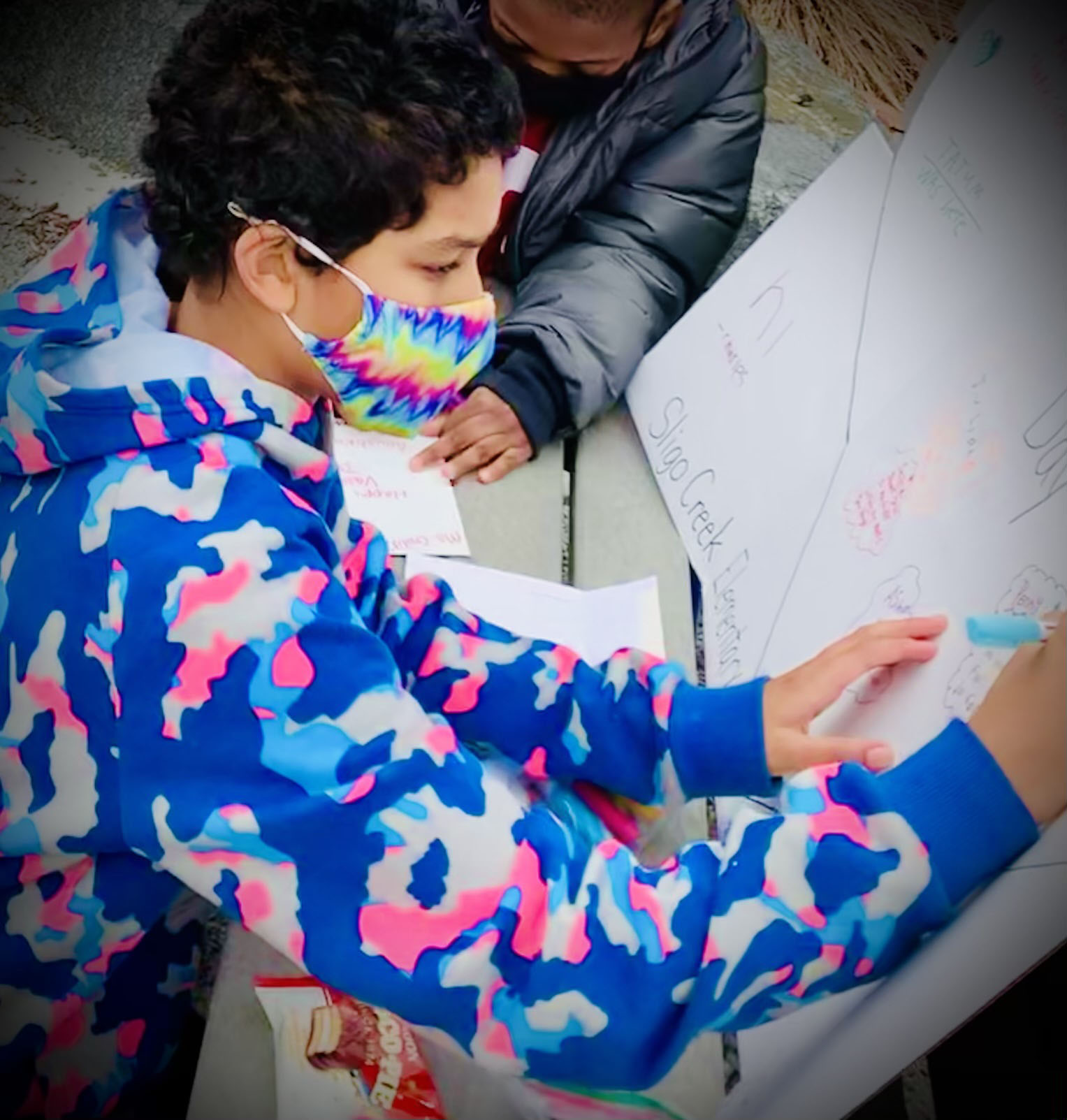Young boy in colorful jacket and mask signs a Valentine's Day card for his teacher